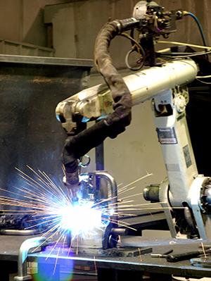 A robot welding arm at TMCO